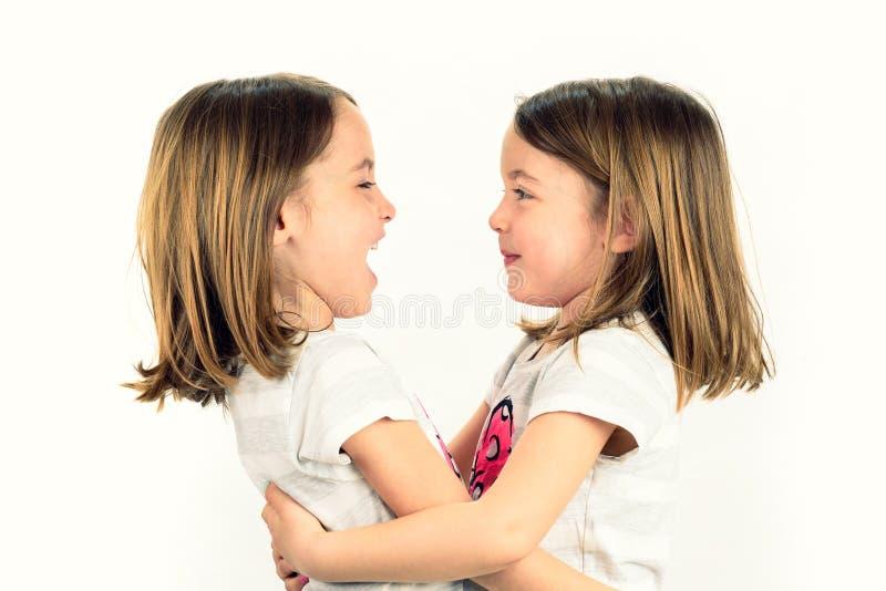 _tweeling meisje kijken bij elkaar en glimlachen royalty-vrije stock afbeeldingen