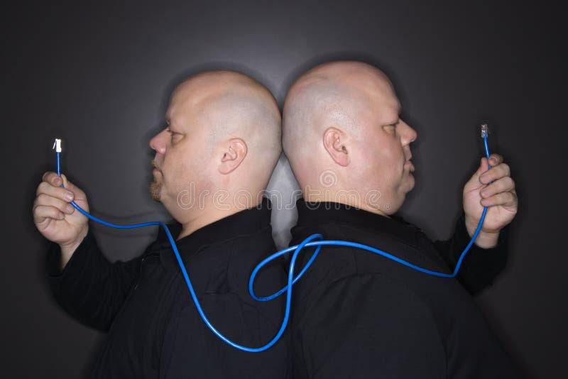 Tweeling mensen die kabel houden. royalty-vrije stock fotografie