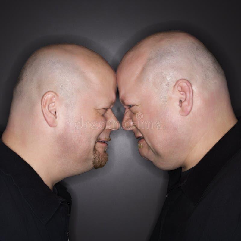 Tweeling mensen die weg onder ogen zien. stock foto