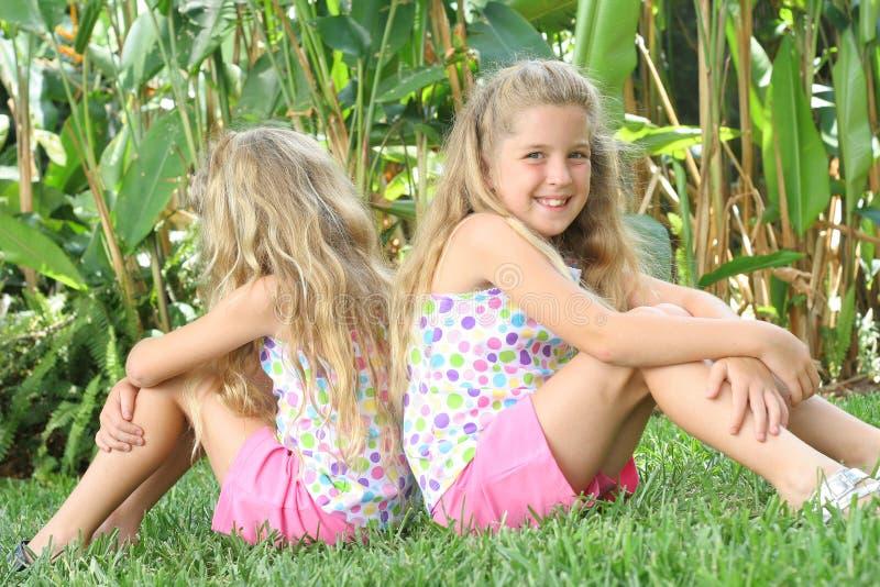 Tweeling zusters buiten in gras royalty-vrije stock foto