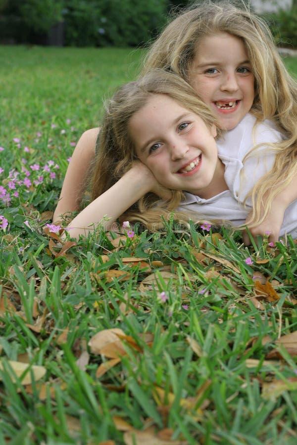 Tweeling zusters die in de grasverticaal leggen stock afbeeldingen