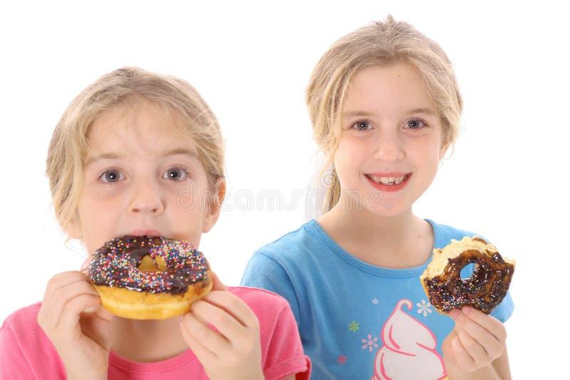 Tweeling zusters die een doughnut eten stock afbeeldingen