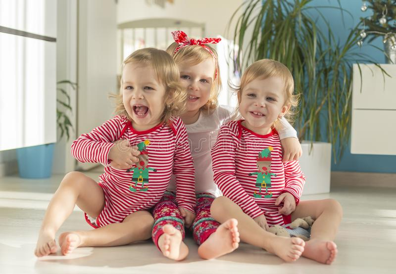 Tweelingen en oudere zusterzitting thuis royalty-vrije stock foto's