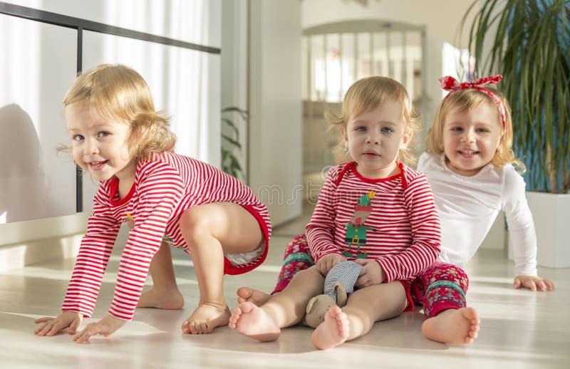 Tweelingen en oudere zusterzitting thuis stock foto
