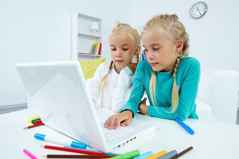 Tweelingen met laptop royalty-vrije stock fotografie