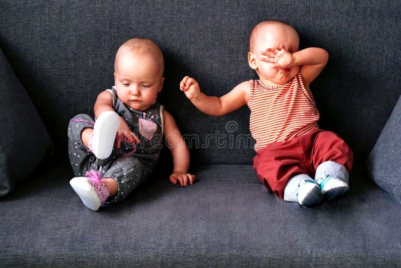 Tweelingen tot een jaarzitting op een grijze bank Broer en zuster stock afbeeldingen