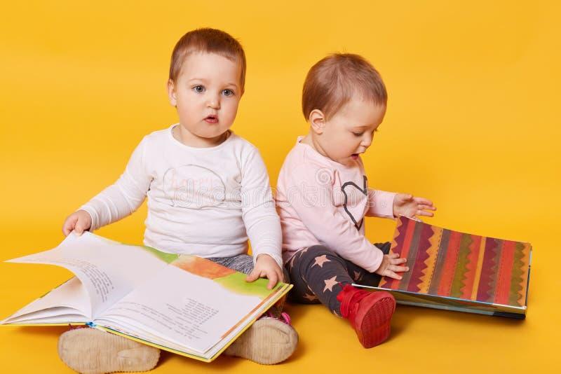 Tweelingenzusters het lezen boekt terwijl thuis het zitten op vloer die, meisjes charmeren die terwijl hun mama die breackfast, m royalty-vrije stock afbeelding