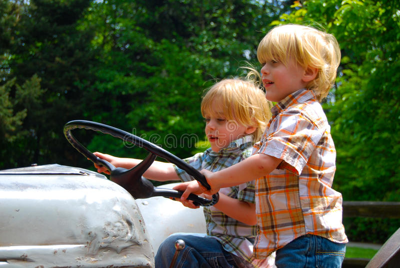Tweelingjongens die tractor drijven royalty-vrije stock afbeeldingen