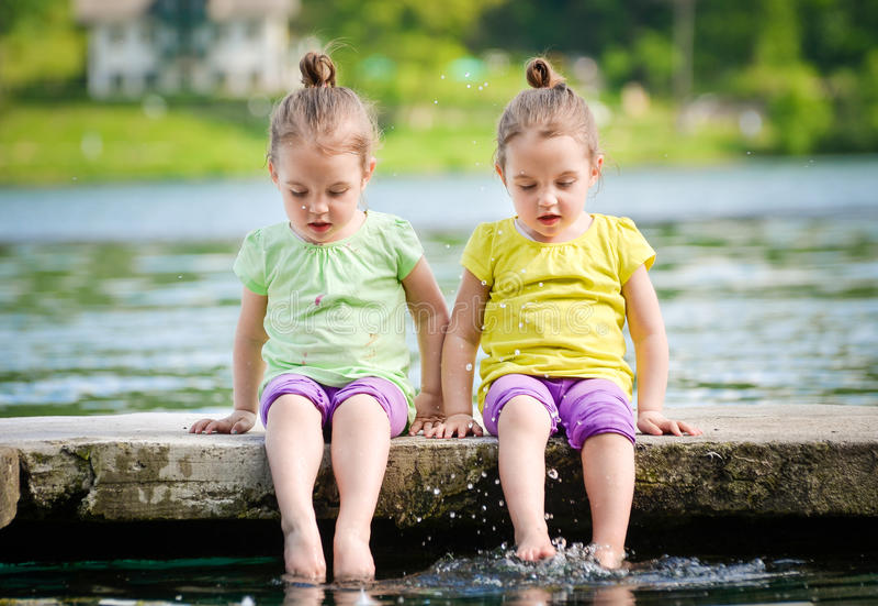 Tweelingmeisjes die op een meerkust uitoefenen stock afbeeldingen