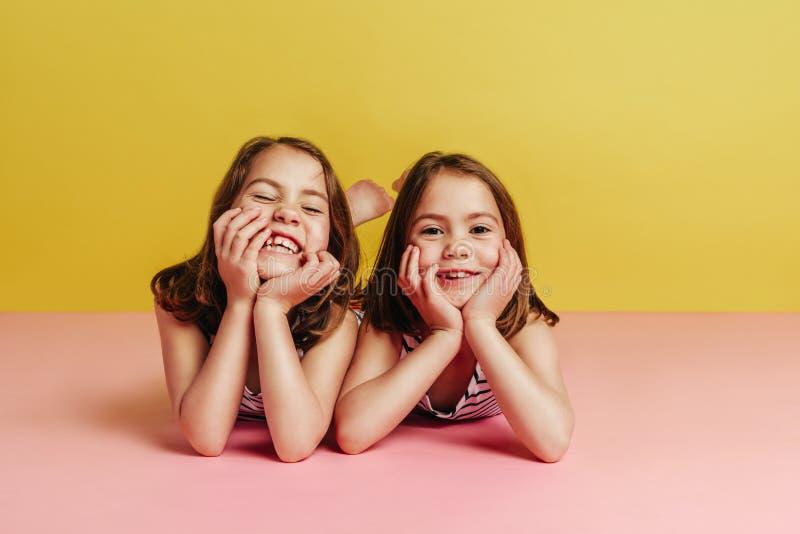Tweelingmeisjes die op roze vloer liggen royalty-vrije stock foto's