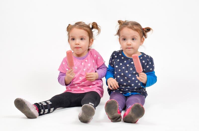 Tweelingmeisjes die roomijs eten stock foto's