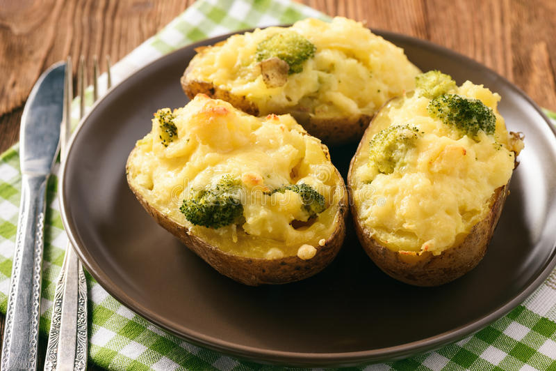 Tweemaal aardappelen in de schil met broccoli, zure room en kaas worden gevuld die stock fotografie