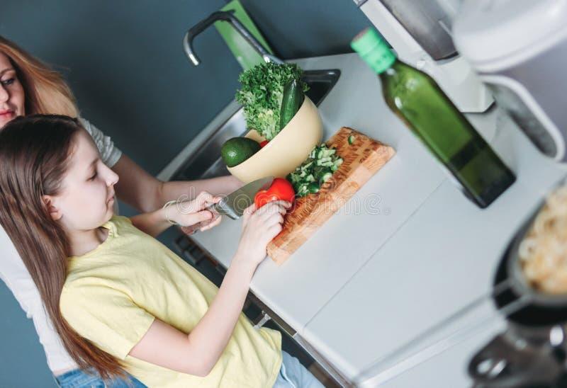 Tween κορίτσι και η μητέρα της που κατασκευάζουν τη φυτική σαλάτα στην κο στοκ φωτογραφία με δικαίωμα ελεύθερης χρήσης