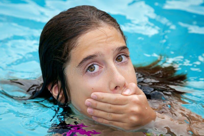 Tween, das ihren Mund bedeckt stockbilder