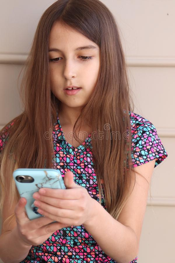 Tween Girl Checks Cell Phone for Messages stock images