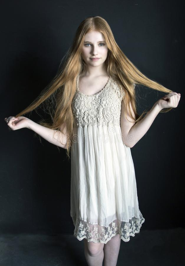 Tween with red hair. Beautiful girl with long red hair royalty free stock photos