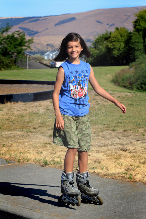 Tween roller blading. A cute young tween girl on roller blades in a park. Shallow depth of field royalty free stock photos