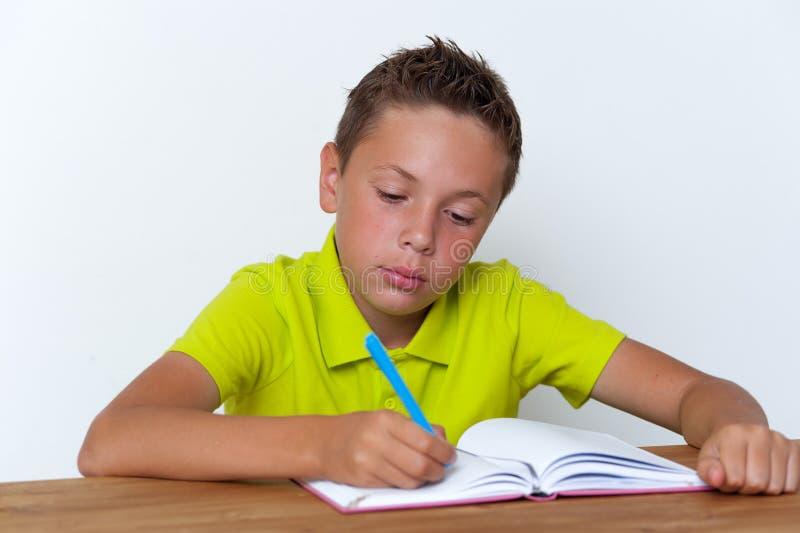 Tween ucznia obsiadanie przy writing i stołem fotografia royalty free