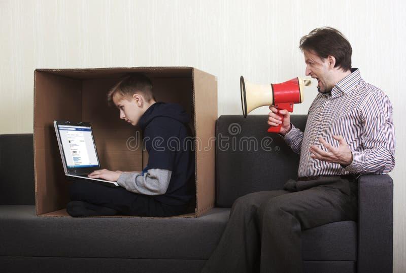 Tween zoonszitting in een kartondoos met laptop terwijl zijn vader bij hem door een megafoon schreeuwt stock afbeelding
