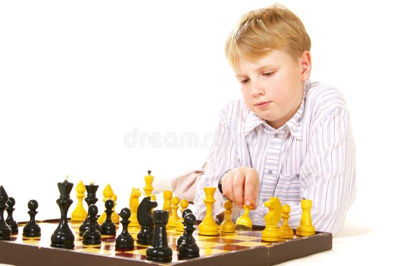 Tweenjunge, der Schach spielt stockbilder
