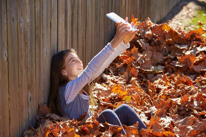 Tweenkindermädchen selfie Tabletten-PC im Herbstlaub stockfotografie