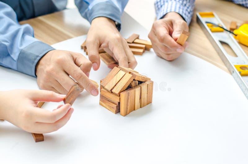 Tweepersoons men vrouwenarchitect trekt een plan, op groot blad van document bij bureau en bouwt modelhuis van houten blokkenbars royalty-vrije stock foto's