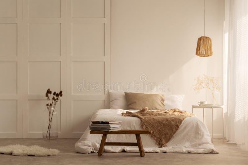 Tweepersoonsbed in de modieuze slaapkamer van wabisabi van minimaal stijlhuis, echte foto stock foto's