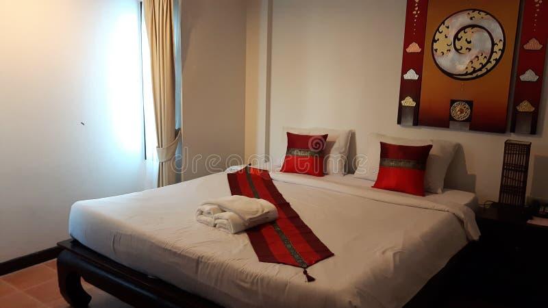 Tweepersoonsbed langs Wit Beddegoed en Wit Rood Hoofdkussen met moderne het beeldmuur van de kunst warme toon op de achtergrond stock afbeeldingen