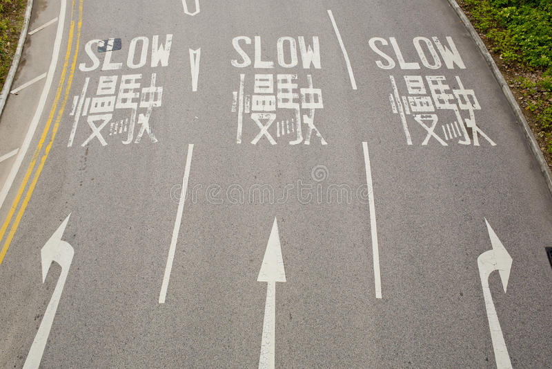 Tweetalige (Engels en Chinees) Langzame verkeersteken voor bestuurder stock foto