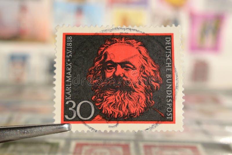 Tweezer holds postage stamp of Germany 150th Birth Anniversary of Karl Marx stock image