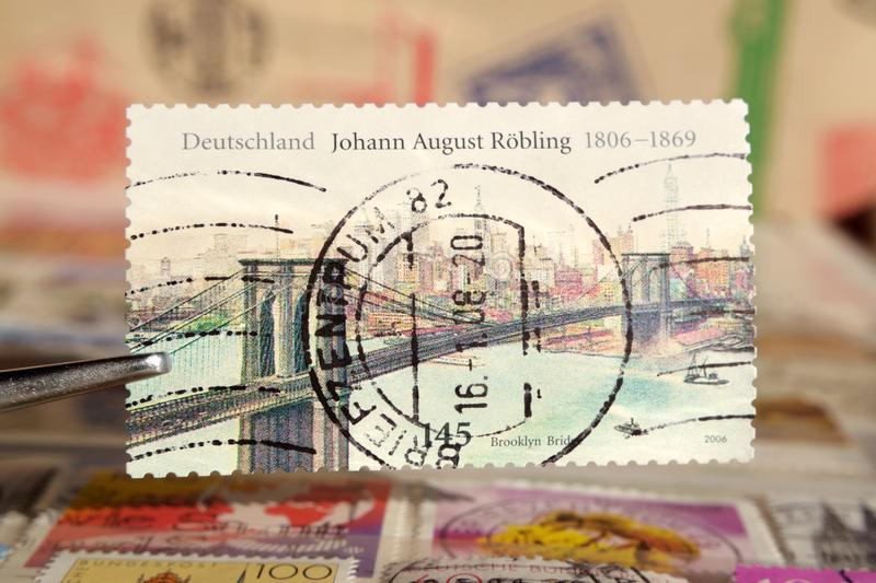 Tweezer holds postage stamp printed by Germany on topic Anniversaries, Shows Johann August royalty free stock photos