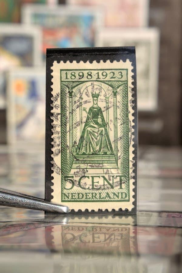 Tweezer houdt postzegel door Nederland op onderwerpstaatshoofden wordt gedrukt, toont Koningin die Wilhelmina stock afbeelding
