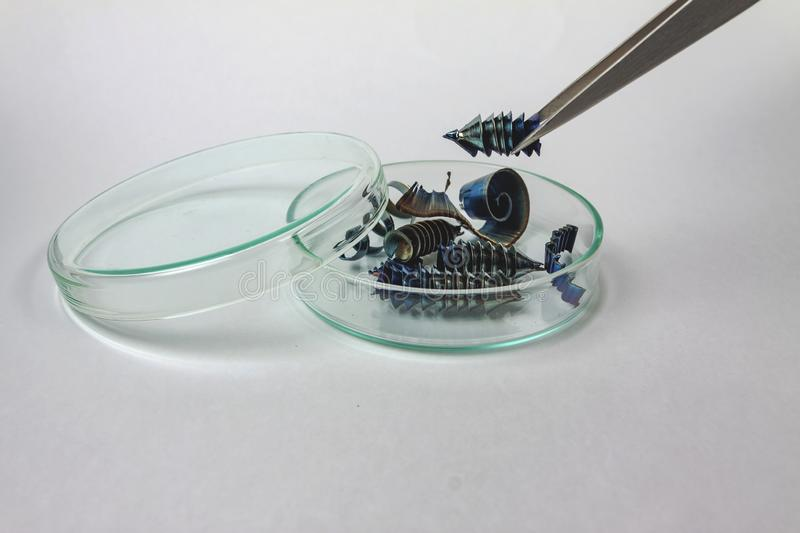 Tweezers holding metal shavings over a small amount of metal shavings royalty free stock photo