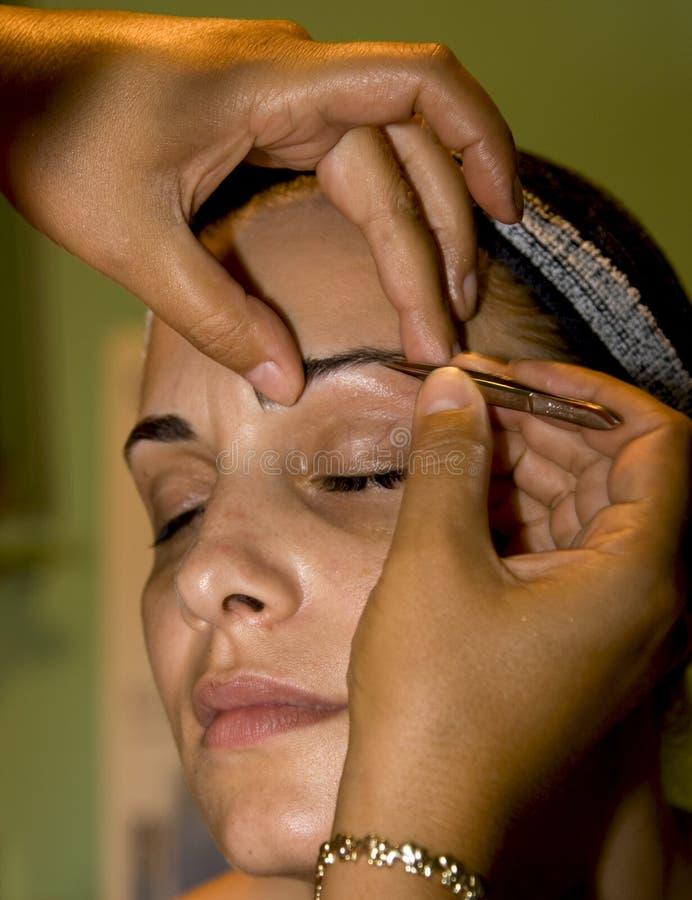 Tweezing eyebrow. Girl tweezing eyebrow at cosmetic royalty free stock images