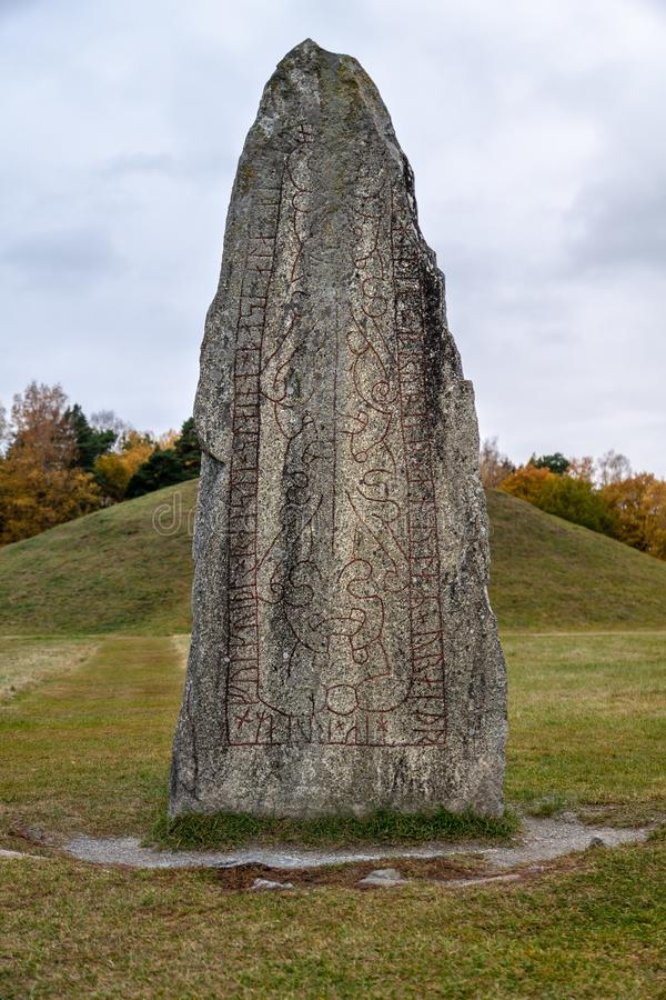 Close up of a large rune stone. Twelve hundred year old rune stone with red runes, located at a large burial ground at Anundshög in Sweden royalty free stock images