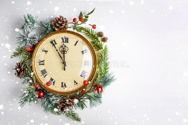 Twelve o`clock, like New Year`s Eve. Gold vintage clock in a Christmas decor on a white background. Copy space. Twelve o`clock, like New Year`s Eve. Gold royalty free stock images