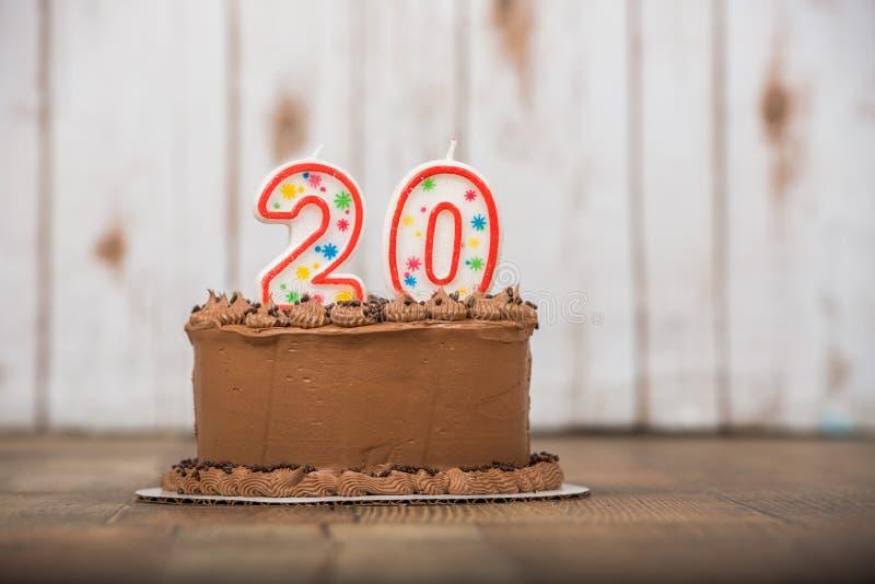 Twentieth chocolate frosted birthday cake. Chocolate frosted cake with 20 or twenty candles on it royalty free stock photography