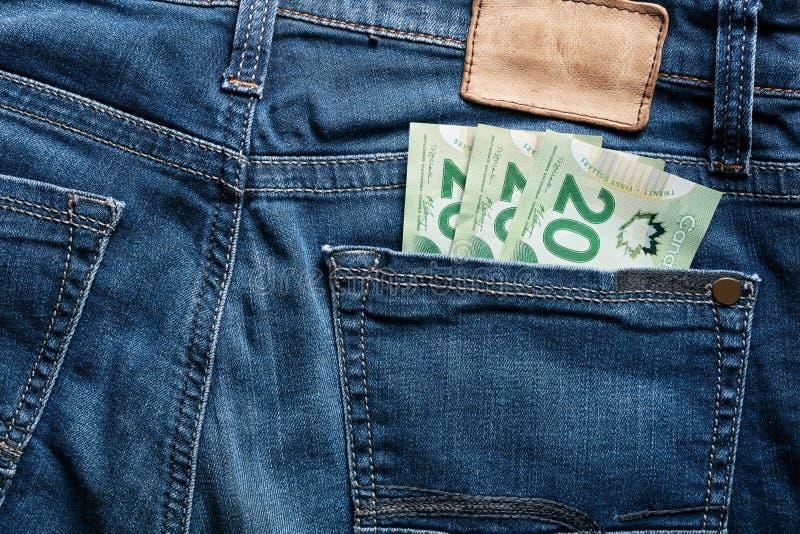 Twenty Canadian dollar CAD bills in the back pocket of a jeans stock images