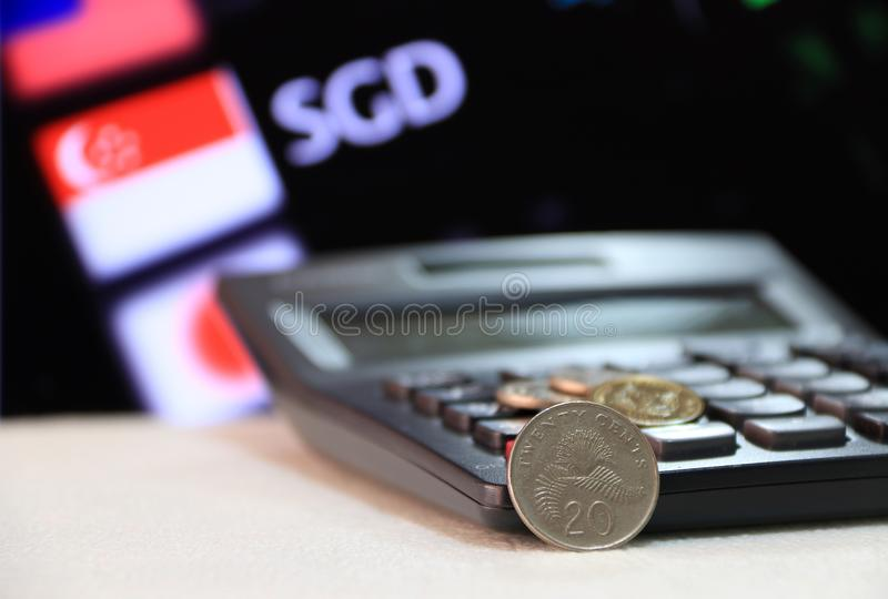 Twenty cents Singapore coin on reverse SGD with black calculator and digital board of currency exchange money background. Twenty cents Singapore coin on reverse stock photos