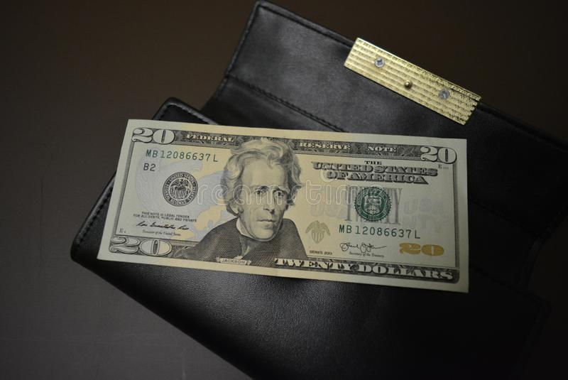 Twenty dollars is on a black wallet made from genuine cowhide leather. One banknote, US currency and dream. Payment for services,. One banknote, US currency and royalty free stock photo