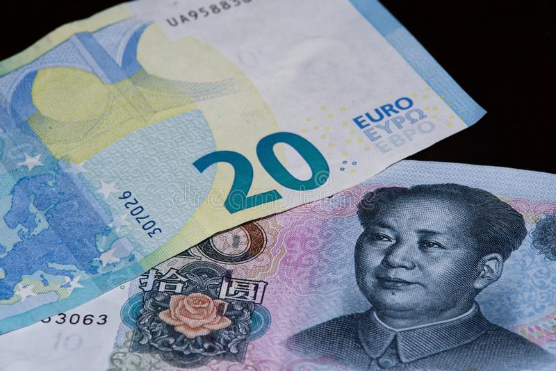 Twenty euro banknote above ten Chinese yuan on black background royalty free stock photography