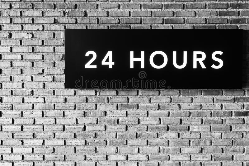 Twenty four hours glowing sign on brick wall, black and white s. Tyle stock photo