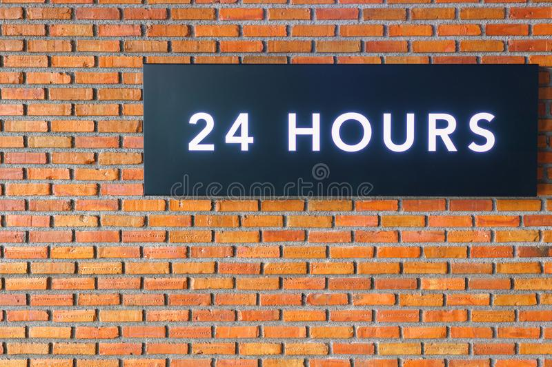 Twenty four hours glowing sign on brick wall.  royalty free stock photography