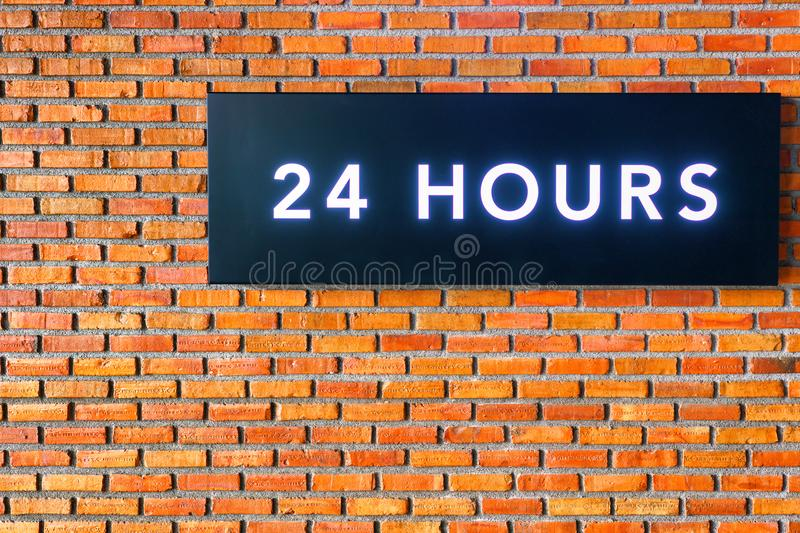 Twenty four hours glowing sign on brick wall.  royalty free stock photo