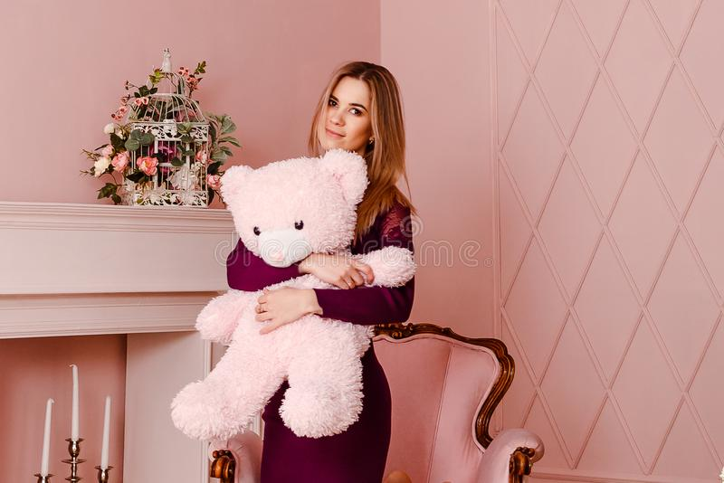 Twenty-year-old woman in a Burgundy dress holding a big pink Teddy bear. Indoors royalty free stock photos