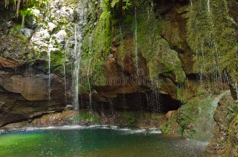 """Twentyfive 25 sources fall down into a grotto at the levada small channel called """"Rabacal"""" in Madeira, Europe. Beautiful grotto as a sightseeing stock images"""