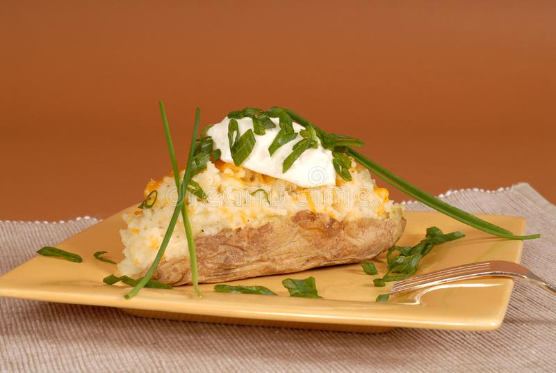 Twice baked potato with chives and sour cream royalty free stock photos