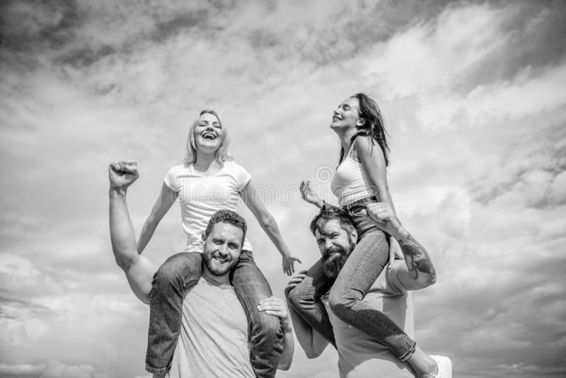 Twice fun on double date. Couples in love having fun. Men carry girlfriends on shoulders. Summer vacation and fun. Couples on double date. Inviting another royalty free stock image