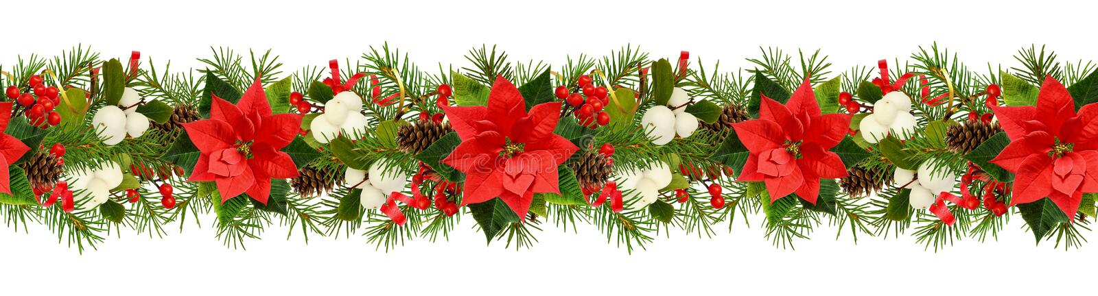 Twigs of Christmas tree, poinsettia flower, berries and holiday decorations in seamless garland stock photo