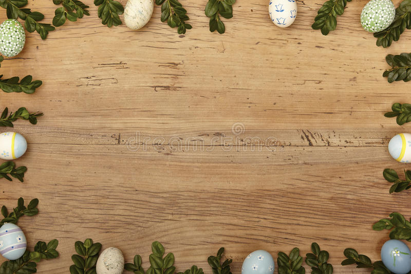 Twigs and easter eggs as frame on wood, copy space stock image